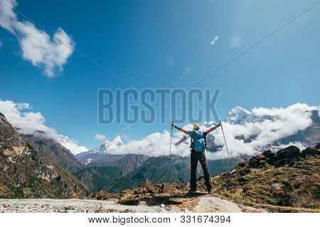 Young Hiker Backpacker Man Rising Arms With Trekking Poles Enjoying The Thamserku 6608m Mountain Dur