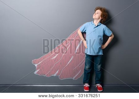 Boy As A Super Hero. Kid Is Looking Up And Posing With A Red Superman Cape Depicted With Chalk On A