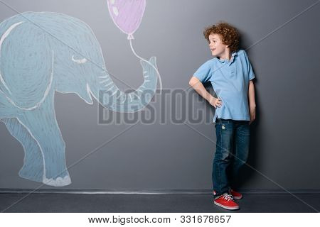 Little Elephant Gives A Balloon To Shy Boy. Young Guy Standing With Arm On Hip And Looking At The An