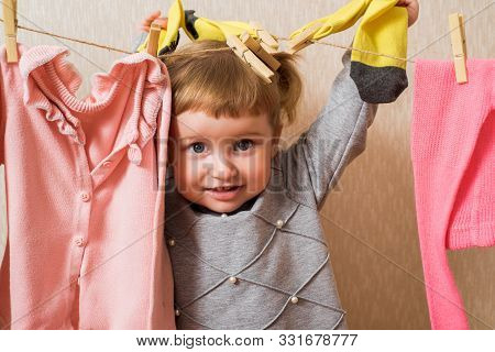 Funny Girl With Clothespin And The Clothesline. Baby Pink Clothes Dry On A Rope. Baby Hangs Yellow S