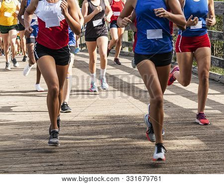 Many High School Girls Running In A Cross Country 5k Race Crossing Over A Wood Bridge At Sunken Mead