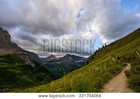 Hiker Heads Through The Trail With Bear Grass Growing On Slopes