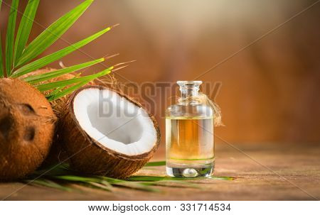 Coconut palm oil in a bottle with coconuts and green palm tree leaf on brown background. Coco nut closeup. Healthy Food, skin care concept. Vegan food. Skincare treatments. Aromatherapy