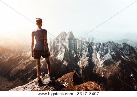 Silhouette of a female climber reaching the summit. Hiker on top of a mountain