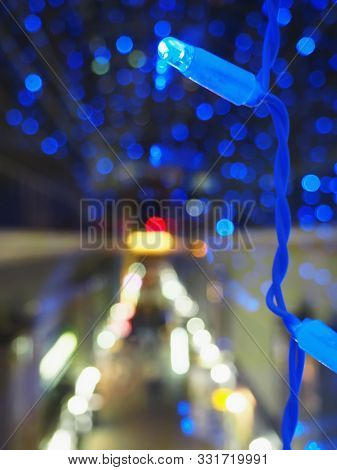 Christmas Theme With Blue Lights. Blurred Image Of Prospekt In The Dark. Bokeh Of Streetlights At Ni