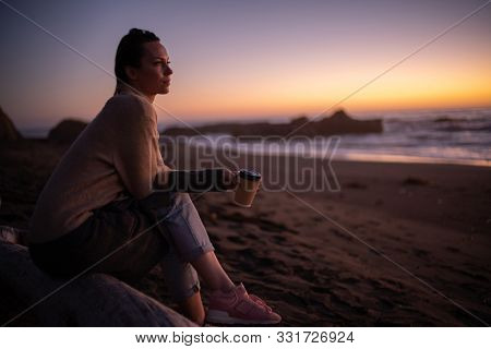 Woman enjoying hot drink on a sunset near ocean