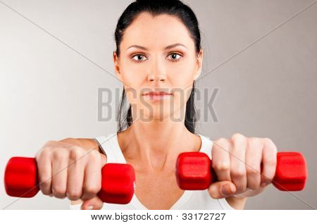 sporty woman is holding two red barbells on grey background and looking at camera