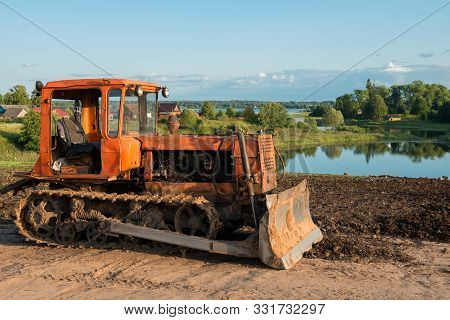 Caterpillar Agricultural Tractor Dt-75 In The Countryside, On The Lake. Lake Focus