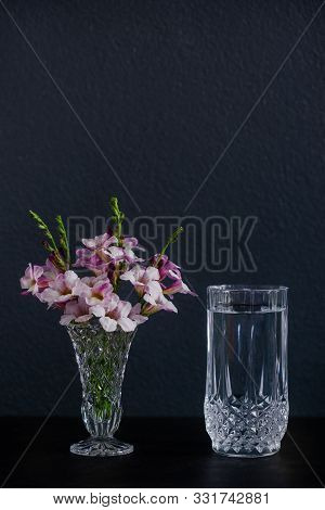 A Glass Of Water And Purple Flowers In A Vase Placed On The Table