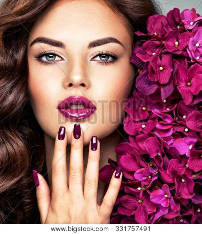Beautfiul Woman's face with vivid make-up of lips and fingernails. Closeup face with flowers. Young caucasian gorgeous adult girl with long brown curly hair. Model. Vivid make-up. Violet fingernails