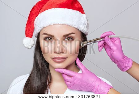 poster of Cosmetologist does the procedure Microdermabrasion on the face of a beautiful woman in a Santa Claus hat. New Year's and Cosmetology concept.