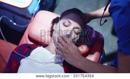 Young Woman In Ambulance, Corpsman Put On Her Face Mask.