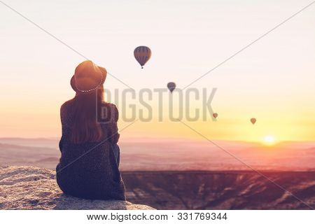 A Woman In Solitude Sits On Top Of A Mountain And Admires The Flight Of Hot Air Balloons In Cappadoc