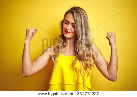 Young attactive woman wearing t-shirt standing over yellow isolated background showing arms muscles smiling proud. Fitness concept.