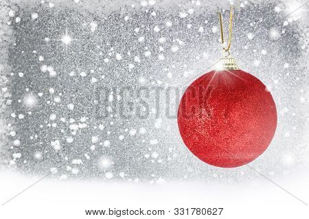 Hanging Christmas Ornaments Over Bokeh Background. Red Christmas Ball Hanging Over Snow During A Sno