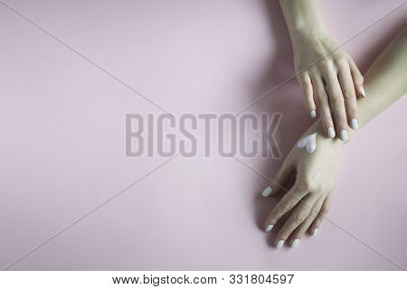 Two Hands With Manicure In Pastel Pink Colors On A Pink Background. Hand Care, Hygiene. Spa Treatmen
