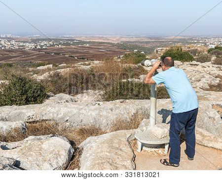 Rosh Haayin, Israel, October 31, 2019 : Tourist Looking Through Stationary Binoculars From A Place C