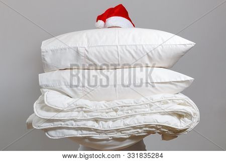 Woman In Santa Hat Holding A Warm Duvet And Feather Pillows Against A Gray Wall. Stack Of Bedding Fo