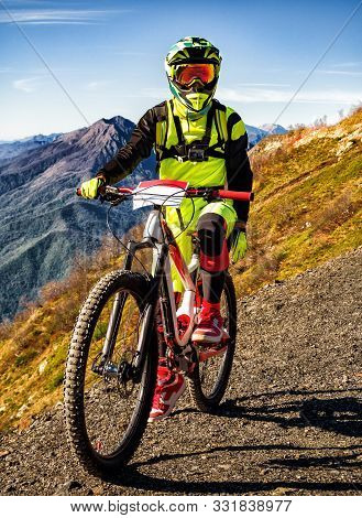 Front view of downhill bicyclist standing with full-suspension mountain bike at sunny summer day poster