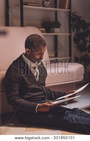 Discouraged African American Man Sitting On Floor And Holding Utility Bills