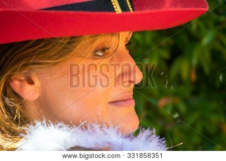 Happy showy young woman in a beautiful red wide-brimmed hat. Background dense evergreen hedge. Concept - portrait and advertising photo
