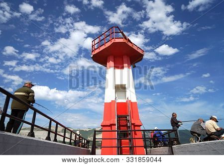 Novorossiysk, Russia - May, 2014: Lighthouse on the pier. Fishermen with fishing rods on the pier, engaged in fishing.