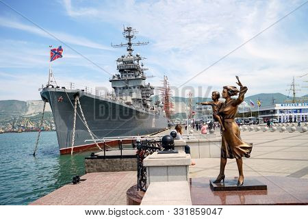 Novorossiysk, Russia - May, 2014: Monument to the wife of a sailor. Bronze sculpture of a woman with a child in her arms, opposite the cruiser
