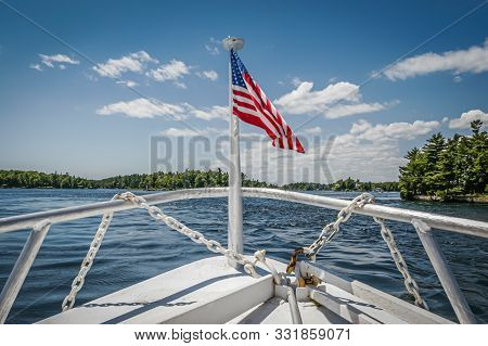 A Tour Boat Displaying The American Flag On The Front Deck Cruises The Waterway Of The Thousand Isla