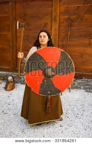 Gudvangen, Norway - June 13 - The Young Woman In National Clothes With Old Axe And Shield In The Vik
