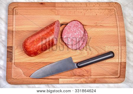 Pieces Of Chopped Sausage And A Kitchen Knife Lie On A Wooden Cutting Board.
