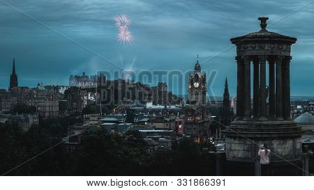 Night Panorama Of The City Edinburgh And Firework At Time Of Festival, View Of The Monument Of Dugal