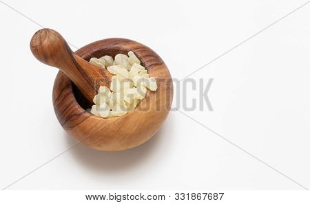 Mastic resin tears. Chios mastic in a wooden mortar isolated on black background poster