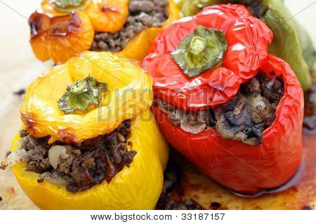 Colourful bell peppers or capsicums stuffed with a filling of ground beef, mushroom, onion and celery, straight from the oven.