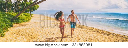 Couple beach vacation banner walking happy travel vacation summer holiday panoramic. Young people holding hands having fun running on tropical getaway for winter holidays.