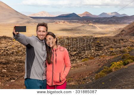 Selfie couple tourists taking self-photo picture with mobile phone on travel vacation. People summer lifestyle woman and man holidaying visiting Lanzarote Timanfaya National Park, Canary Islands.