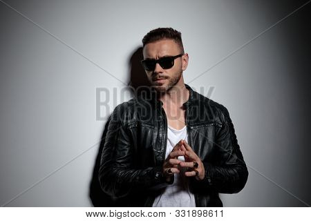 Tough fashion man playing with his fingers and planning while wearing sunglasses, standing on gray studio background