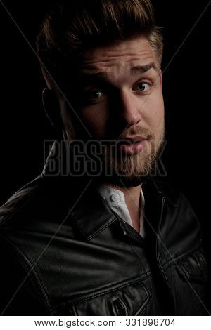 close up of a beautiful casual man wearing leather jacket staring at camera intrigued on black studio background