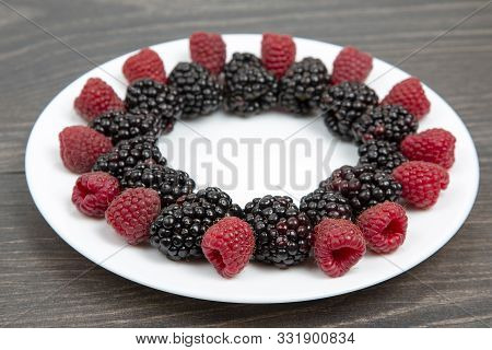 Raspberries And Blackberries On A White Plate. Vitamin And Diet Foo