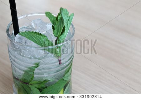 Glass Of Mochito Cocktail On Wooden Table With Black Straw, Ice And Mint Leaf. Copy Space For Text.