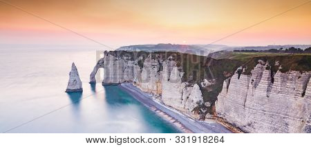 banner of coastal landscape along the Falaise d'Aval the famous white cliffs of Etretat village with the Porte d'Aval natural arch and the rock known as the Aiguille d'Etretat