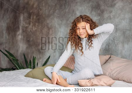 Curly Haired Beautiful Tween Girl In Pajamas Just Waking Up And Sitting On The Bed With Pillow, Morn