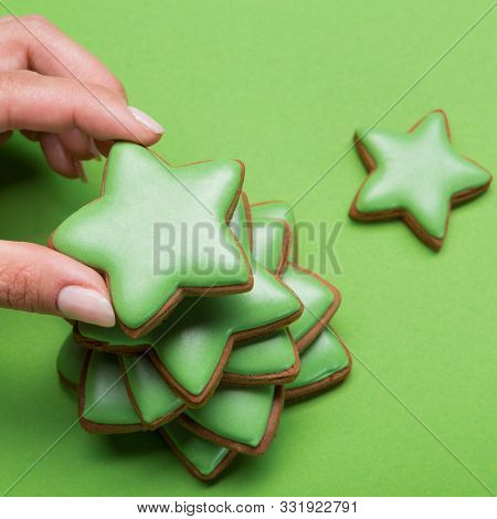 Female Hand Lays Out Gingerbread Christmas Tree, On Green Background, A Lot Of Gingerbread, Christma