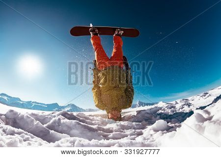 Snowboarder Stands Upside Down On Head Against Mountains. Ski Concept