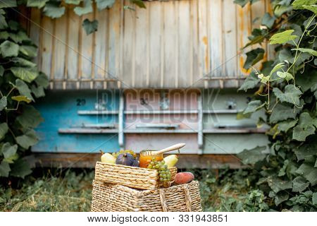 Composition Of Sweet Fruits And Jar Full Of Honey With Woooden Beehives On The Background At The Api