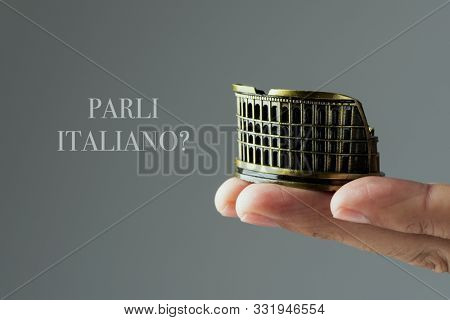closeup of the hand of a caucasian man holding a miniature of the Flavian Amphitheatre or Colosseum, in Rome, Italy, and the question parli italiano? do you speak Italian, written in Italian