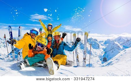 Ski in winter season, mountains and ski family on the top in sunny day in France, Alps above the clouds.