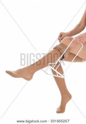 Woman Putting On Compression Garment With Stocking Donner Against White Background, Closeup