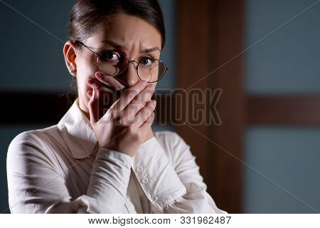 Young Woman In Fear Tightly Covers Her Mouth With Her Hands. Copy Space