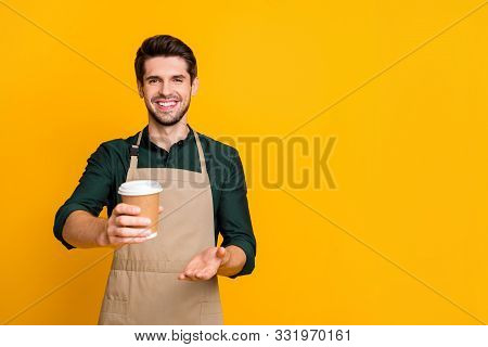 Here Your Latte. Portrait Of Positive Cheerful Guy Student Work Part-time In Coffee Bar Shop Give To
