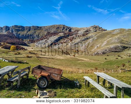 Old Small Sidecar Trailer Barrow For Countryside Work Next To A Wooden Bench And Beautiful Mountain